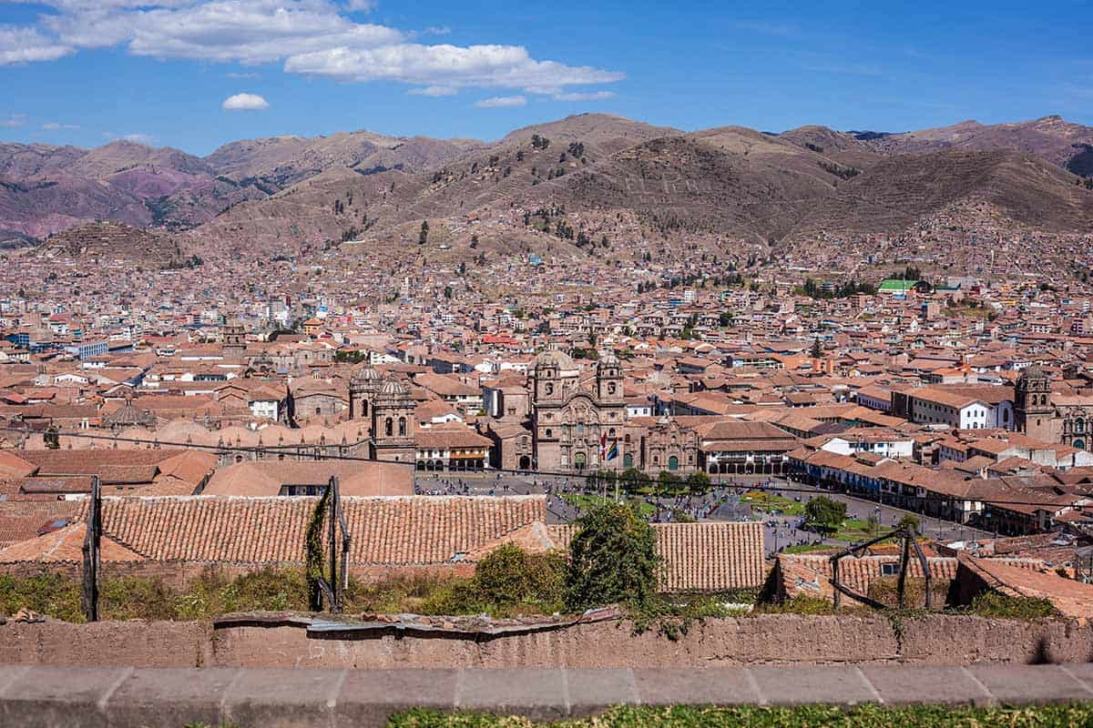 The plaza of Cusco city with red-tiled houses and surrounding Andean hillsides.