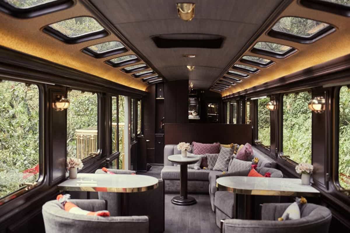 The inside of the Inca Rail Private Train to Machu Picchu with comfortable couches and table seating and large windows.