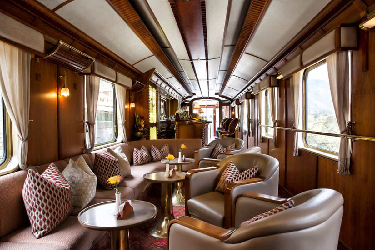 Inside the modern bar car of the PeruRail Belmond Hiram Bingham car. There are comfortable seats and a bartender at the bar.