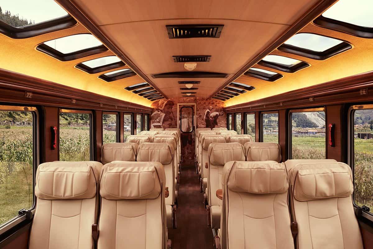 Inside the Inca Rail Machu Picchu Voyager Train with forward facing seats next to the train windows.
