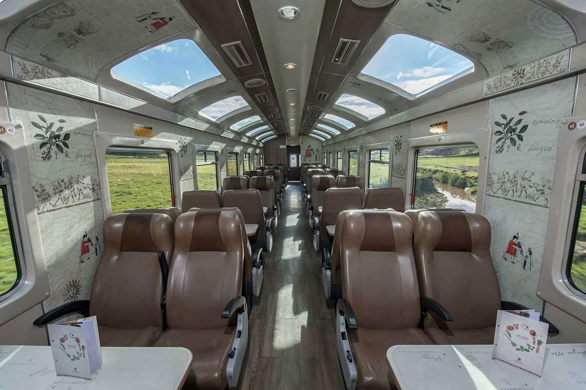 The rows of seats next to windows inside the PeruRail Vistadome Train to Machu Picchu.