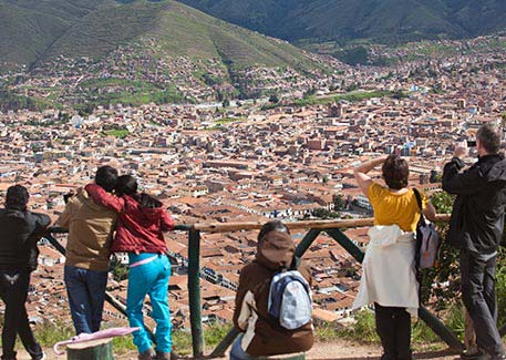 Travelers looking out over the rooftops of Cusco from a hilltop viewpoint.