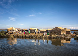 Reed islands in Lake Titicaca with houses on top and locals waving