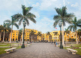 Yellow historical buildings and palm trees in Lima's plaza de armas, the city's main square.