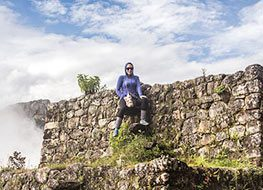 A tourist posing in front of a wall at the archaeological ruins of Machu Picchu.