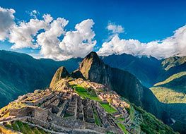The Inca ruins of Machu Picchu with the Andes Mountains as a backdrop on a party cloudy day.