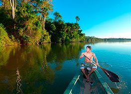 VA shirtless man paddling a canoe down a river in the Peruvian Amazon Rainforest.