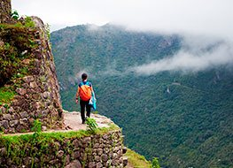 A hiker with a backpack walking along the Inca Trail with a lush green mountain in the distance.