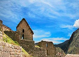 Looking up at Machu Picchu stone structure with clear blue sky above