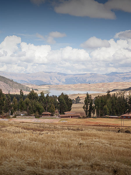 A rustic scene in the Sacred Valley with a few houses, a small forest and a lake visible.