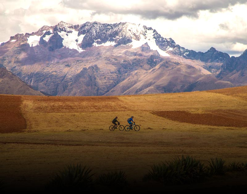 Two cyclists biking through a field in the Sacred Valley with the snowcapped Andes as a backdrop.