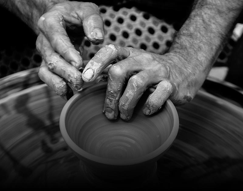 A black and white photo of a Cusco artisan's hands working with a ceramic bowl.