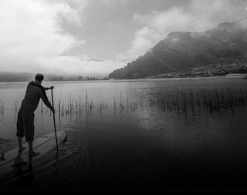 A man enjoying some stand up paddleboarding at Lake Piuray in the Sacred Valley of the Incas.