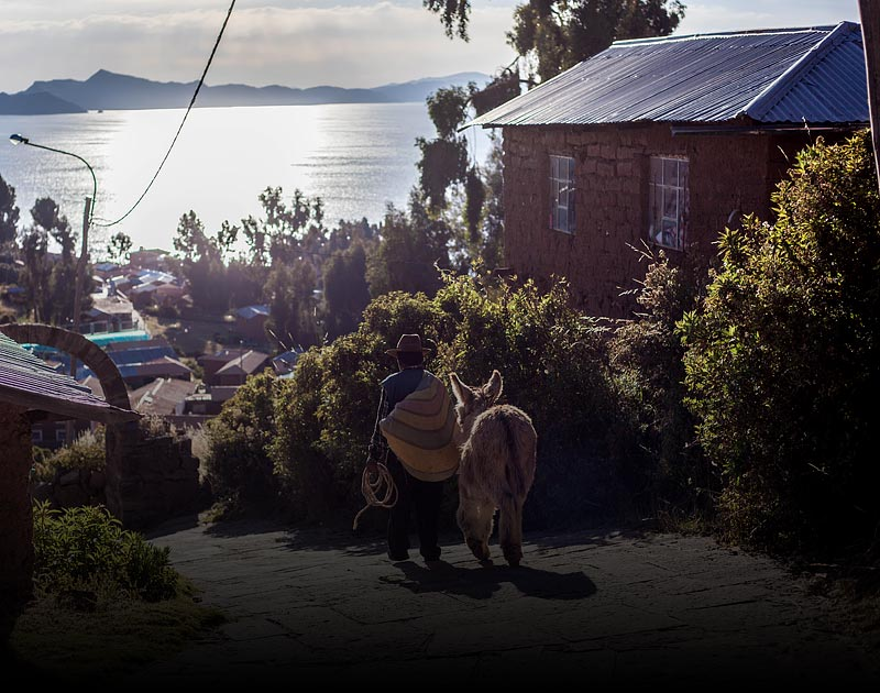 A local villager carrying a sack and walking with a donkey on Amantani Island in Lake Titicaca.