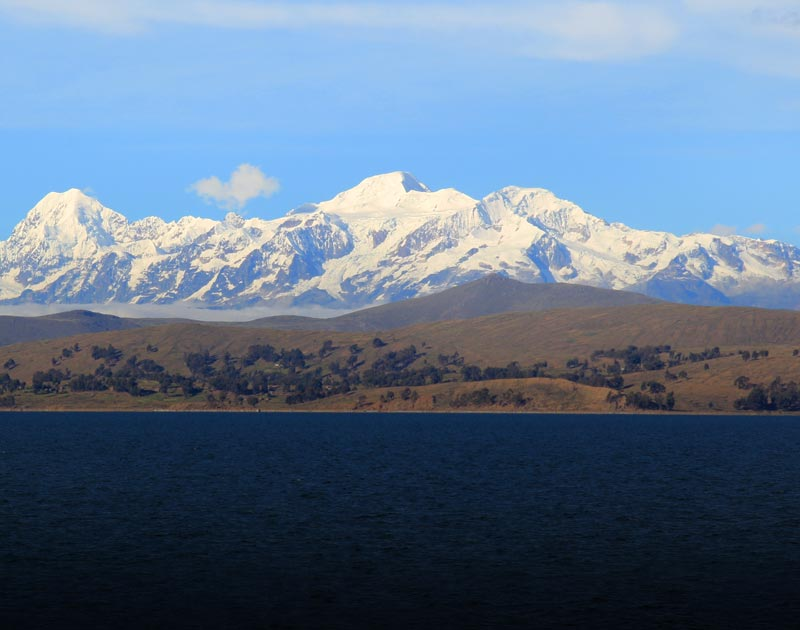 Snow-covered Andean mountains looming over Lake Titicaca, the highest navigable lake on earth.