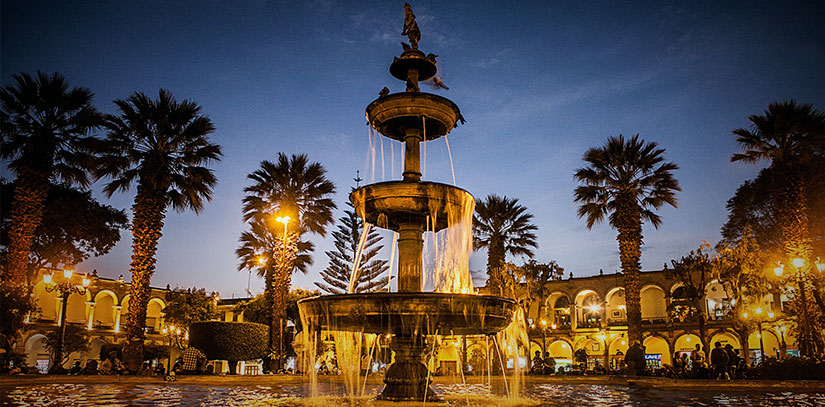 "Fountain, buildings and palm trees at night in the Plaza de Armas of Arequipa, a popular destination of the ""white city"""