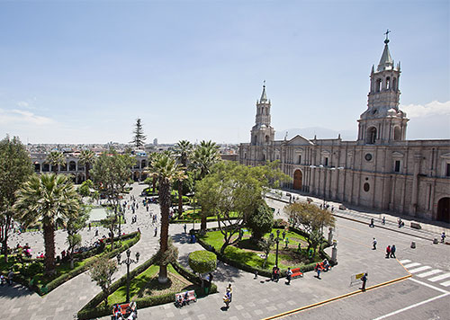 Plaza de Armas of Arequipa, Peru on a clear day, with its characteristic volcanic white stone architecture and palm trees