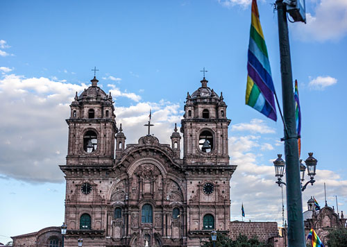Cusco Cathedral of the famous Plaza de Armas, a colonial church built between 1560-1654, with blue skies and Quechua flag