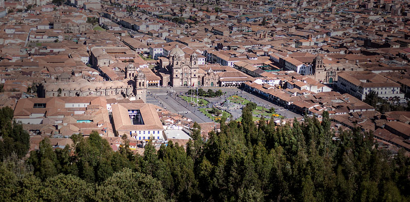 Trees hug the city of Cusco, with its characteristic terracotta roofs and architecture blending Inca and colonial influences