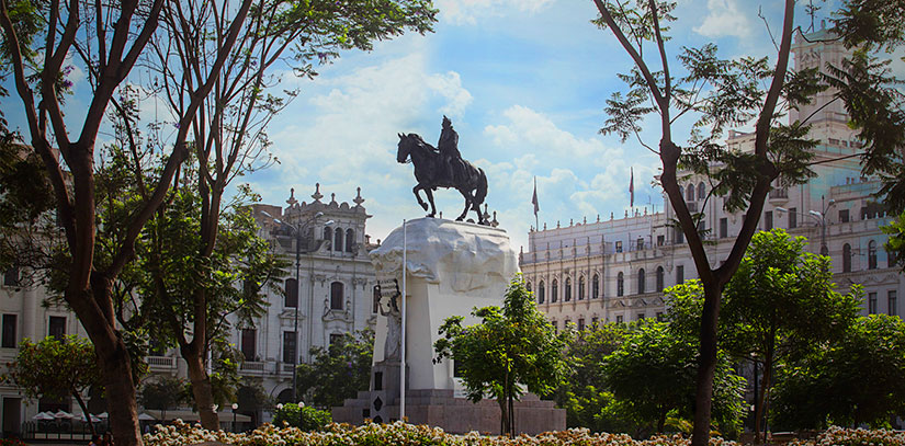 Plaza de Armas in center of Lima on a mostly sunny day with trees, colonial government palacas and a man on horse statue