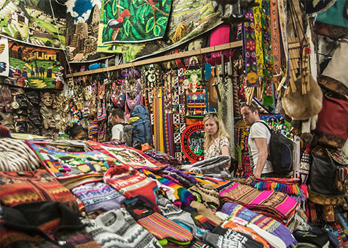 Colorful stand with Peruvian textiles, instruments, jewelry, scarves and other souvenirs at an artisan market in Lima, Peru