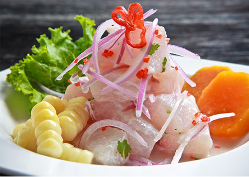 Traditional Peruvian ceviche, which is white fish prepared with lime, red onion and aji with corn and sweet potato side