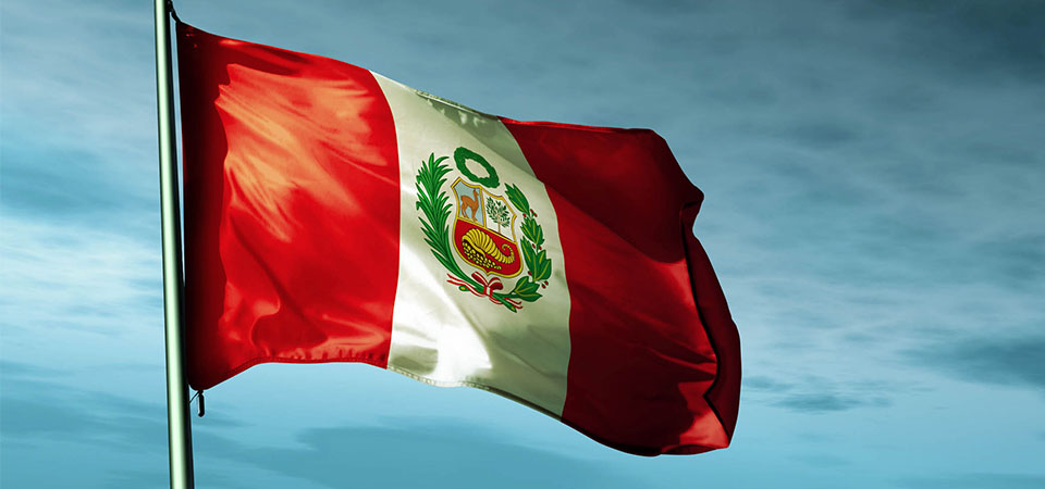 Peruvian flag with its characteristic white and red colors and coat of arms symbol waving in the wind with blue skies