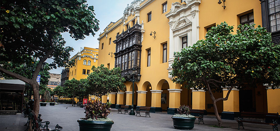 Yellow buildings displaying colonial architecture on a quiet street with trees in the historic district of Lima