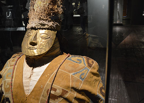 Artifact of man with gold face and burnt orange clothing on display in a museum in Lima, an excellent Peru day tour