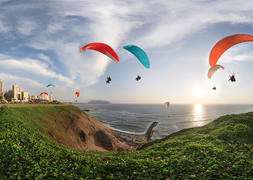 Lima's Pacific Coast with its malecon, parks, buildings and paragliders in the air on a sunny day, a great Peru destination