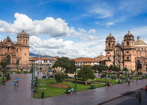 A sunny day with blue skies and white fluffy clouds at the famous Plaza de Armas of Cusco, with colonial architecture
