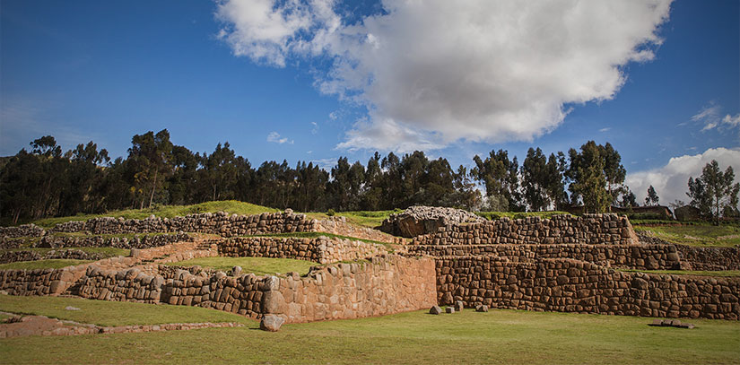 Ruins that display sophisticated Inca stone work located in the lush Sacred Valley of Peru with blue skies and clouds