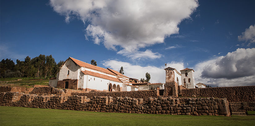 Sacred Valley ruins with colonial structure nestled in the lush greenery of this Andean landscape on a sunny day
