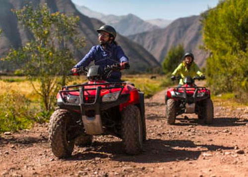 A man and woman traversing through the Andes Mountains on an ATV tour through the Sacred Valley in Peru on a clear day