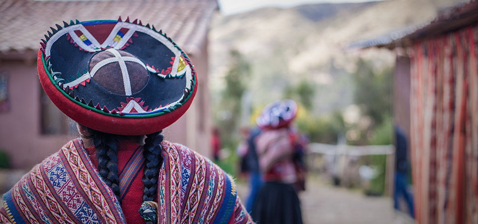 Andean women with braids and traditional hat and attire walking through the village of Chinchero of the Sacred Valley