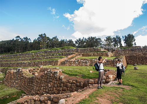 Two travelers exploring ancient ruins displaying iconic Inca stonework in the Sacred Valley on a mostly sunny day