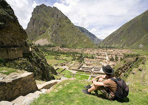 Man sitting on the grass overlooking a small village nestled in the Sacred Valley of the Inca on a partly cloudy day