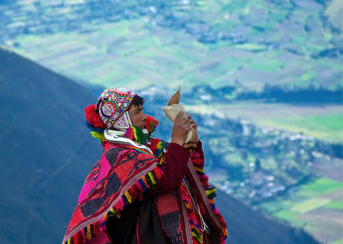 Andean man making an offering to pachamama, or mother earth, in a ceremony to practice ayni, or reciprocity, with the earth