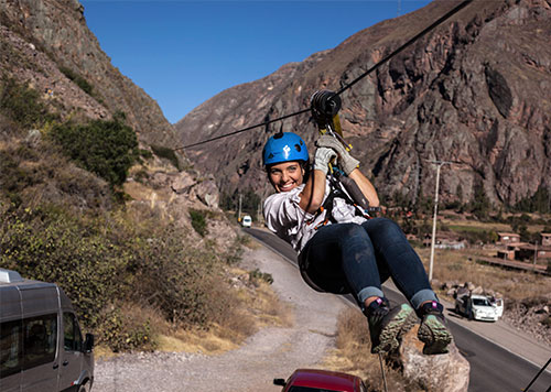 Woman ziplining across the Andean Valleys in the Sacred Valley of the Inca beneath blue skies, a popular Peru adventure tour
