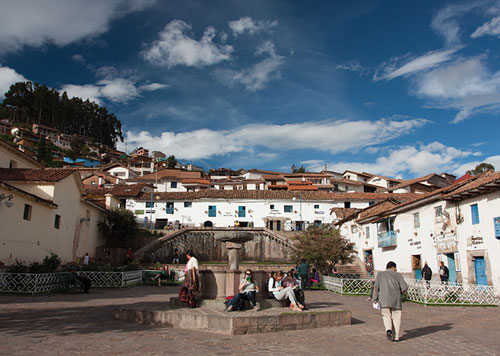 Plazoleta San Blas of Cusco, the artisan corner, with blue skies and wispy clouds over white buildings with terracotta roofs