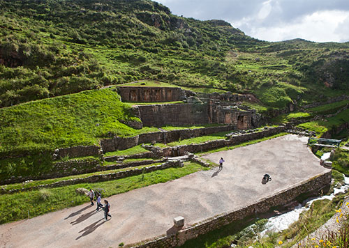 "Tambomachay or ""Inca Baths"" of Cusco, a series of aqueducts and canals, on a overcast day with lush greenery and stream"