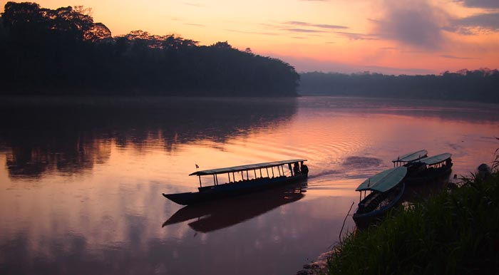 A motorized passenger boat takes off from a small port in the Peruvian Amazon Rainforest.