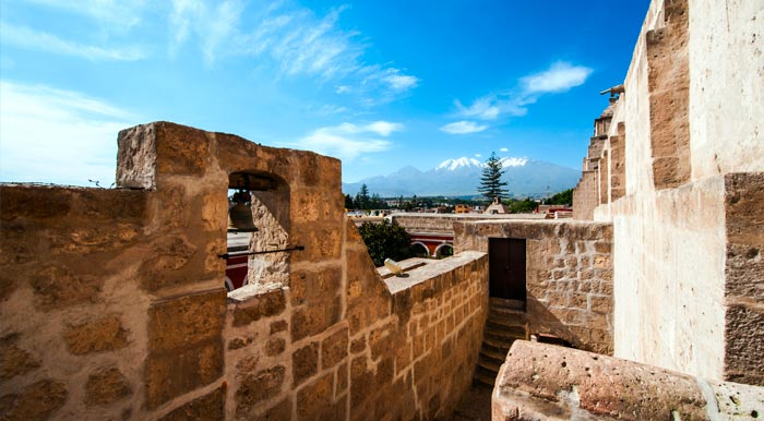 A colonial-era building in Arequipa, with some of the city's volcanoes visible in the distance.