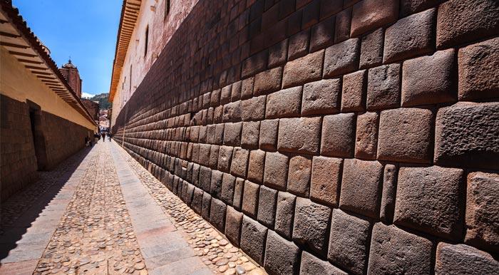 An alleyway running alongside a building featuring impressive Inca stonework in Cusco.
