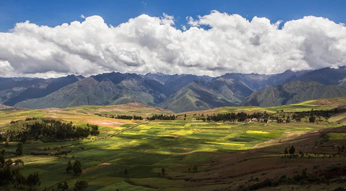 Agricultural fields  with the Andes Mountains as a backdrop in Peru's Sacred Valley.