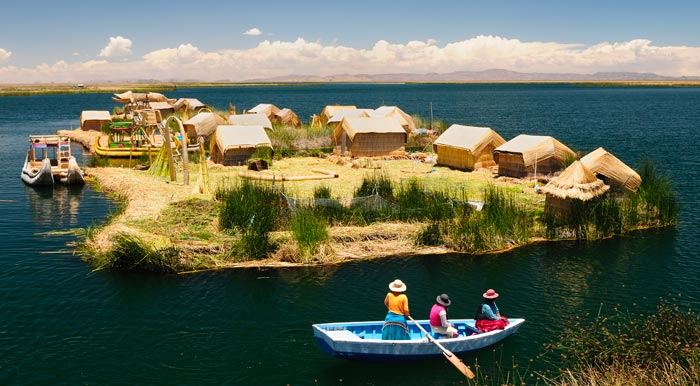 A small rowboat of indigenous women rowing past one of the floating Uros Islands.
