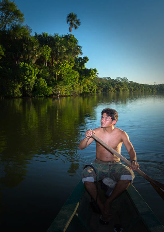 A man rows a boat on a river in the Amazon Rainforest with lush green trees growing on the shore