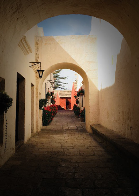 White arches above the entrance to Santa Catalina Monastery with a glimpse of red buildings inside