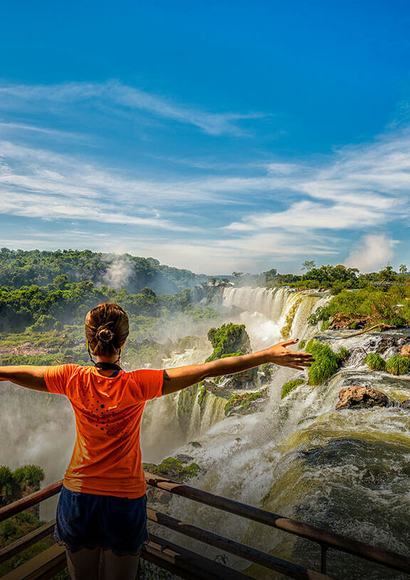 A person stretches their arms to the side while overlooking massive waterfalls at Iguazu Falls