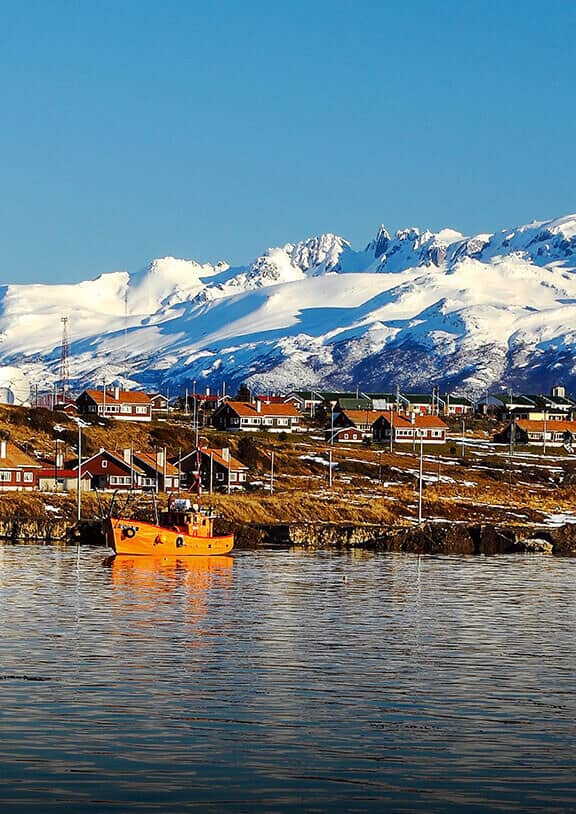 A fishing boat in a lake near Patagonia-style houses with snow-capped mountains in the distance.